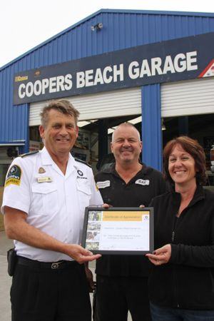 AWARD: Cooper's Beach Garage proprietors Ray and Angela Dare receiving their certificate of appreciation from St John northern region operations manager Mike Burrows.